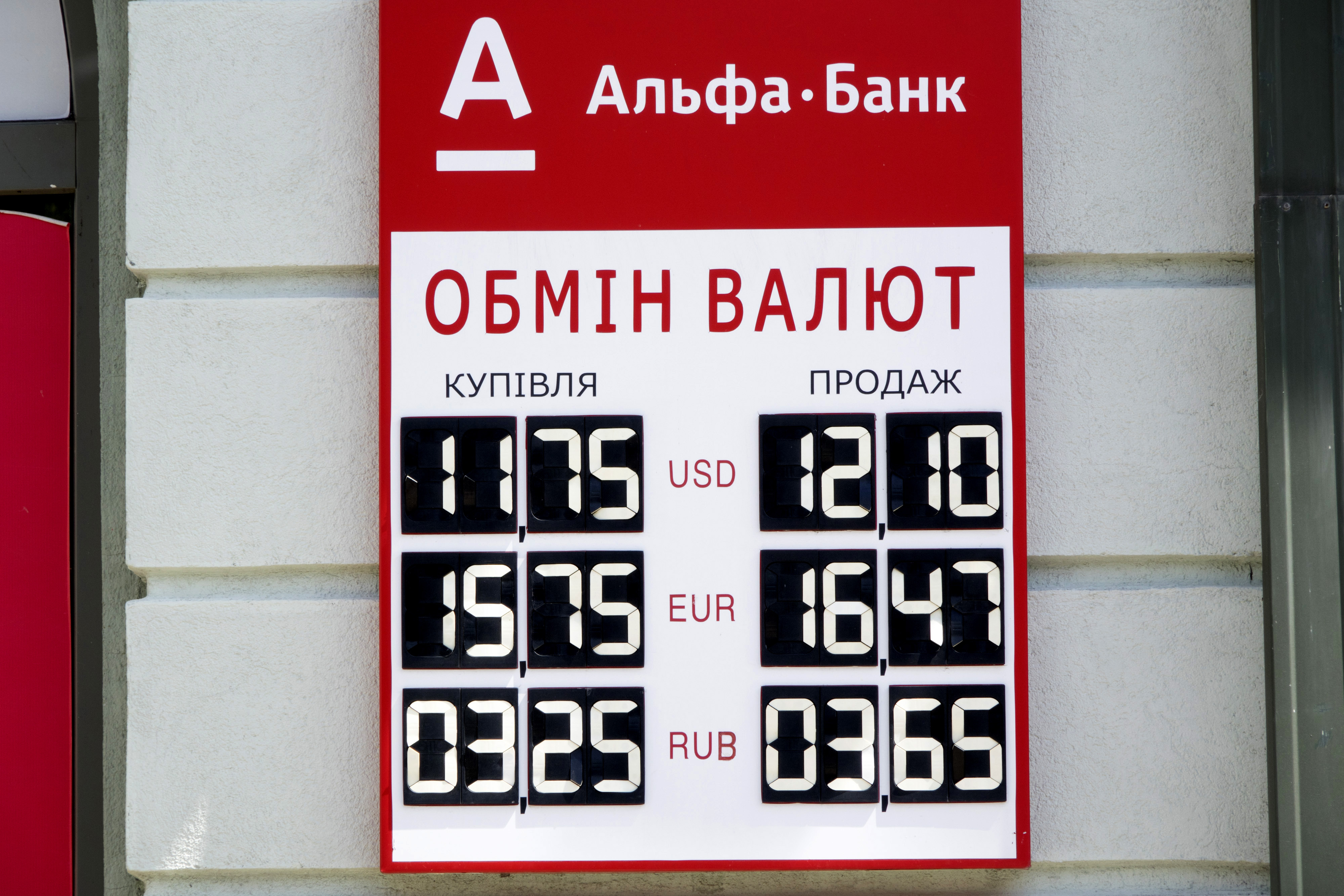 A foreign currency exchange rate sign sits on display outside an Alfa Bank bank branch in Kiev, Ukraine, on Thursday, May 29, 2014. Russia's central bank ordered the Ukrainian units of nine banks to cease operations in Crimea, saying they have failed to meet their obligations to depositors and clients. Photographer: Vincent Mundy/Bloomberg