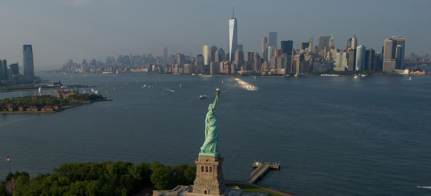 The Statue of Liberty stands ahead of One World Trade Center in the Manhattan skyline in this aerial photograph taken above New York, U.S., on Wednesday, June 10, 2015. U.S. stocks rallied and the dollar fell as the Federal Reserve signaled it will continue to support the economy. Photographer: Craig Warga/Bloomberg