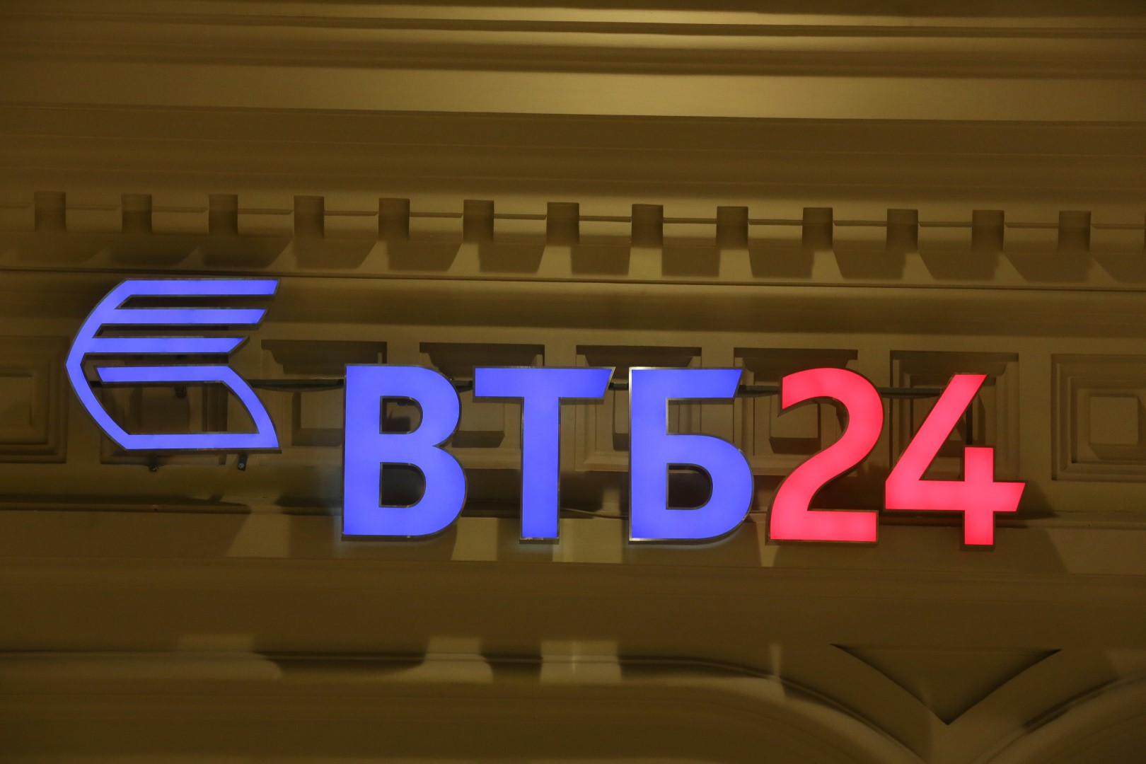 An illuminated sign for Bank VTB 24, a retail unit of state-controlled VTB Group, sits on display above an automated teller machine (ATM) outlet in Moscow, Russia, on Monday, Dec. 22, 2014. The ruble's rout, sparked by falling oil prices and sanctions imposed on businesses including OAO Sberbank, prompted Russians to begin buying luxury goods from Porsche sports cars to Tiffany rings to preserve the value of their savings. Photographer: Andrey Rudakov/Bloomberg