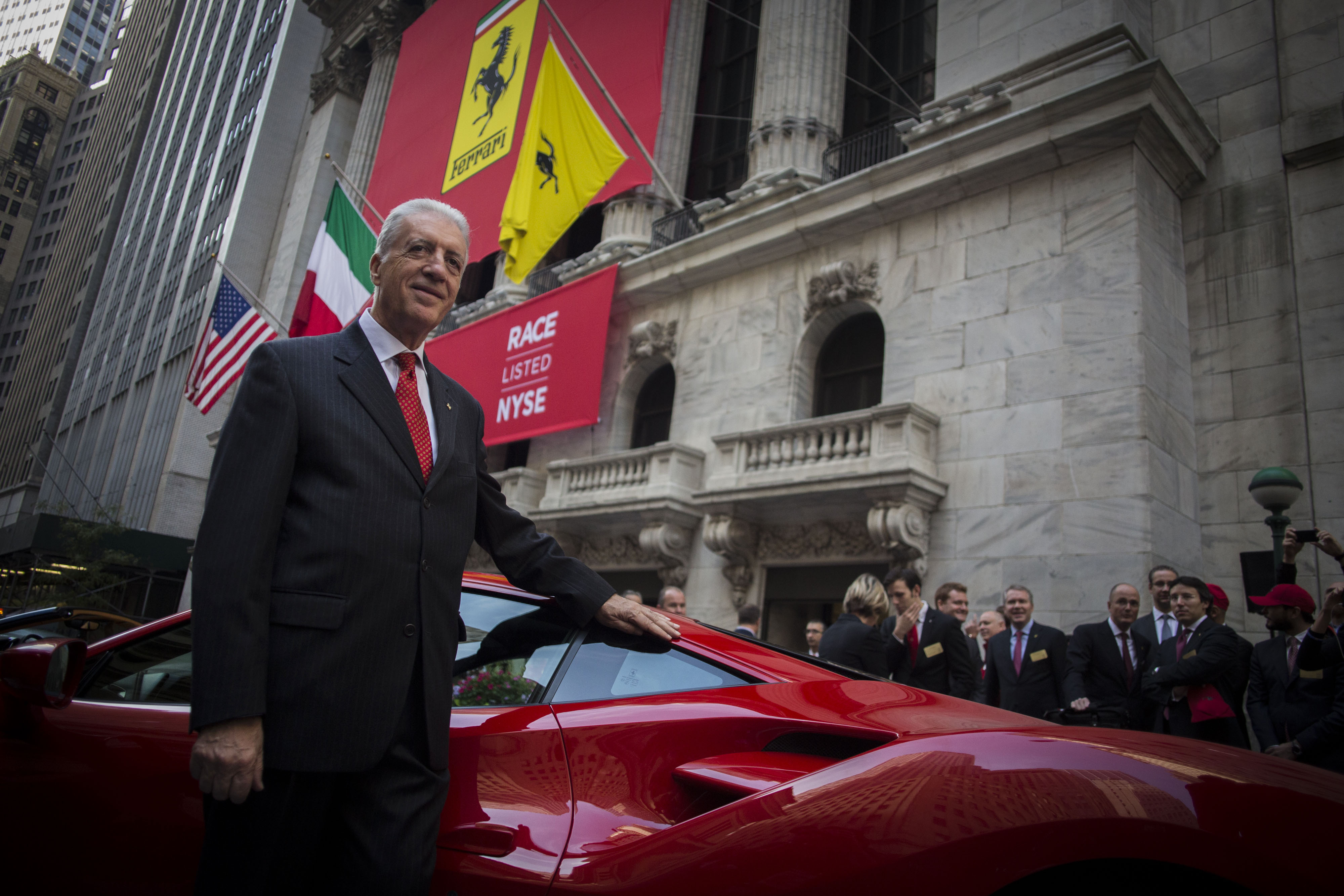 Piero Ferrari, vice chairman of Ferrari SpA, stands for a photograph in front of a Ferrari 488 GTB sports vehicle outside of the New York Stock Exchange (NYSE) in New York, U.S., on Wednesday, Oct. 21, 2015. Ferrari NV climbed as much as 17 percent after its initial public offering, the first step in Fiat Chrysler Automobiles NV's plans to spin off the supercar maker to finance expansion plans. Photographer: John Taggart/Bloomberg *** Local Caption *** Piero Ferrari