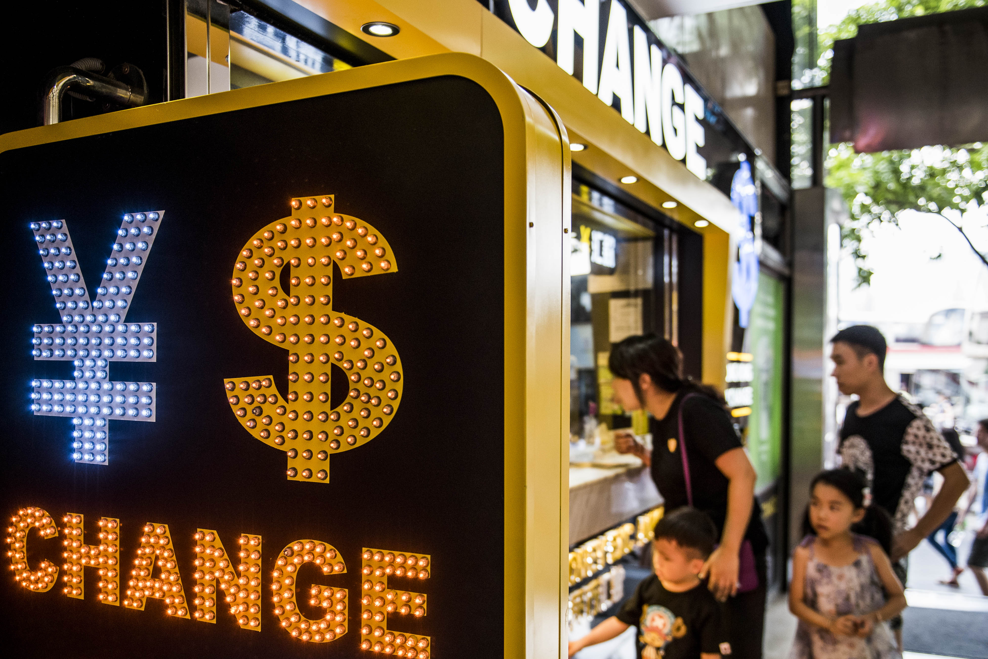 The currency symbol for the Chinese yuan and the dollar is displayed at a currency exchange store in Hong Kong, China, on Wednesday, Aug. 12, 2015. The yuan sank for a second day, spurring China's central bank to intervene as the biggest rout since 1994 tested the government's resolve to give market forces more sway in determining the exchange rate. Photographer: Xaume Olleros/Bloomberg