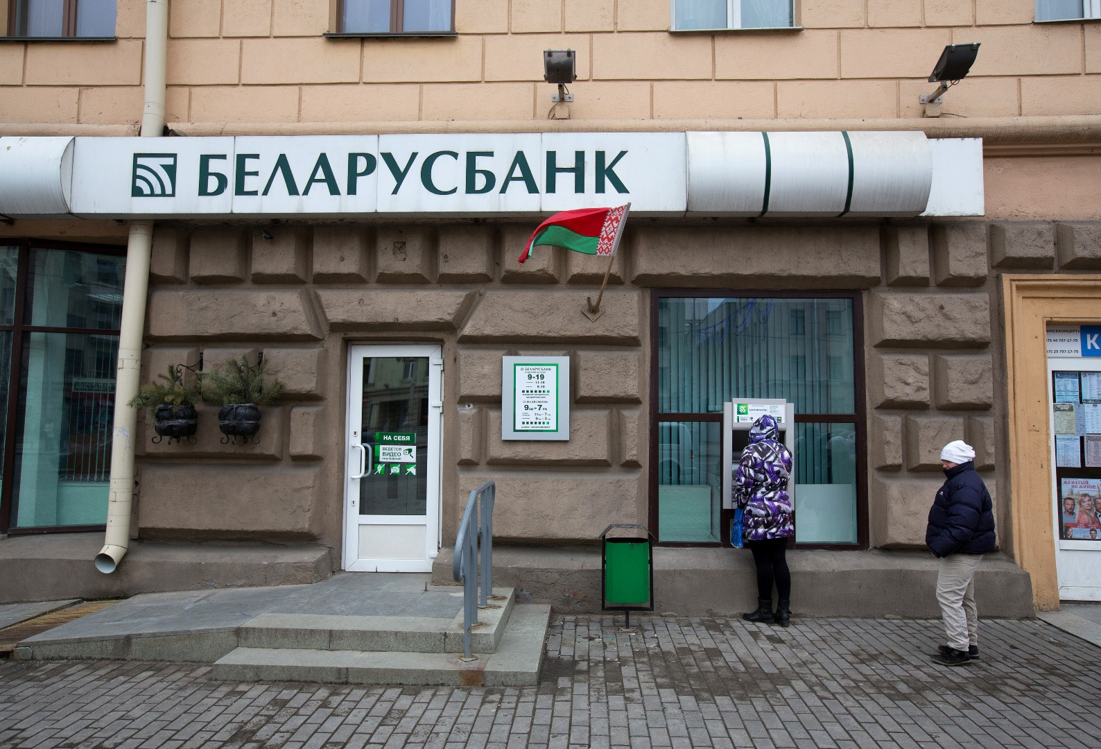 A customer waits to use an automated teller machine (ATM) outside a Belarusbank bank branch in Minsk, Belarus, on Wednesday, March 16, 2016. European Union governments scrapped sanctions on leaders of Belarus in an effort to pry the former Soviet republic out of the shadow of the Kremlin. Photographer: Andrey Rudakov/Bloomberg