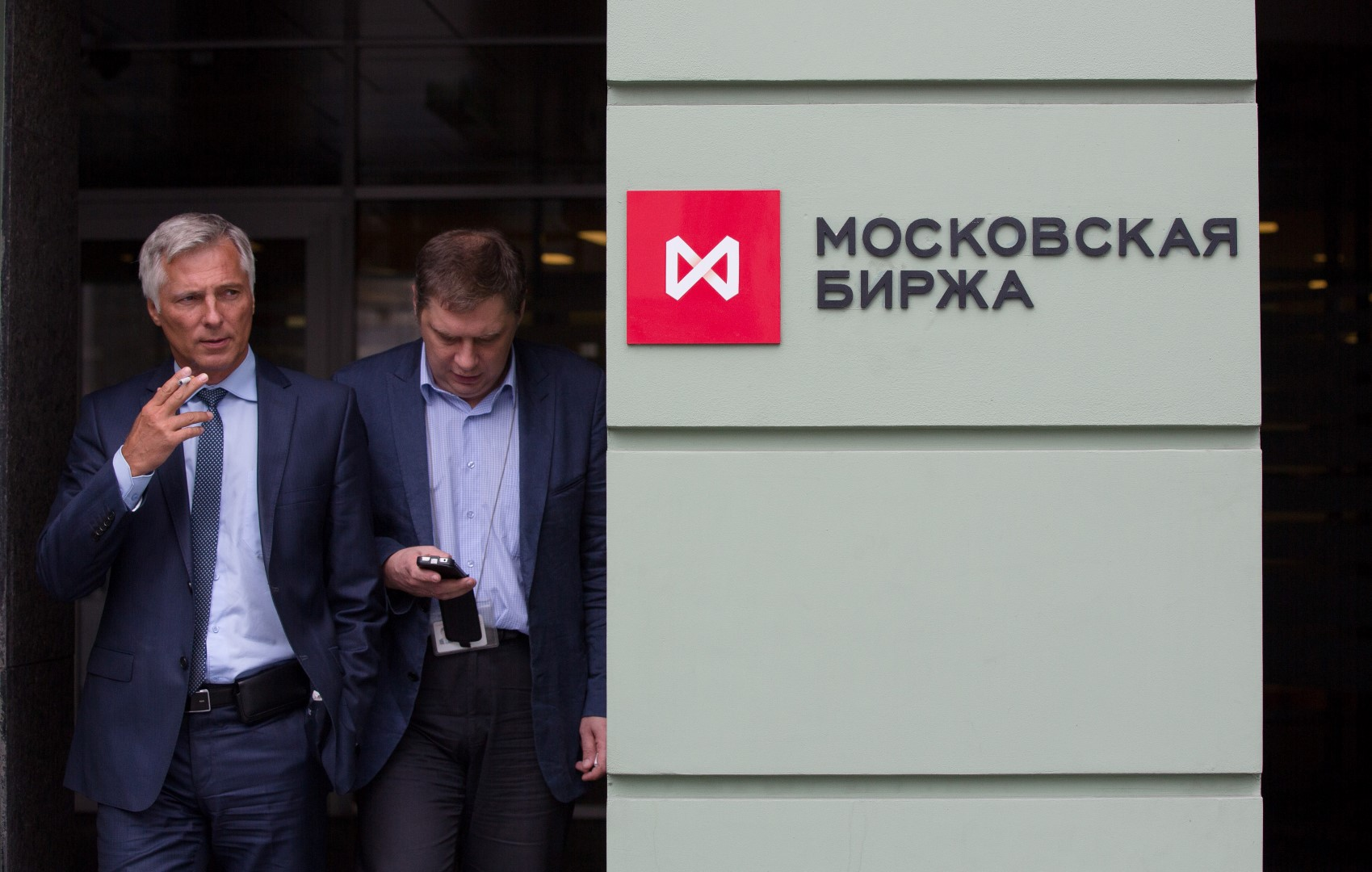Employees stand and smoke in an alcove neae the entrance to the OAO Moscow Exchange in Moscow, Russia, on Thursday, Aug. 29, 2013. Russia's main stock and fixed-income exchange will move on Sept. 2 from the current system of T+0, in which trades must be settled on execution, to a T+2 mode for all equities, Russian depositary receipts and exchange-traded funds. Photographer: Andrey Rudakov/Bloomberg