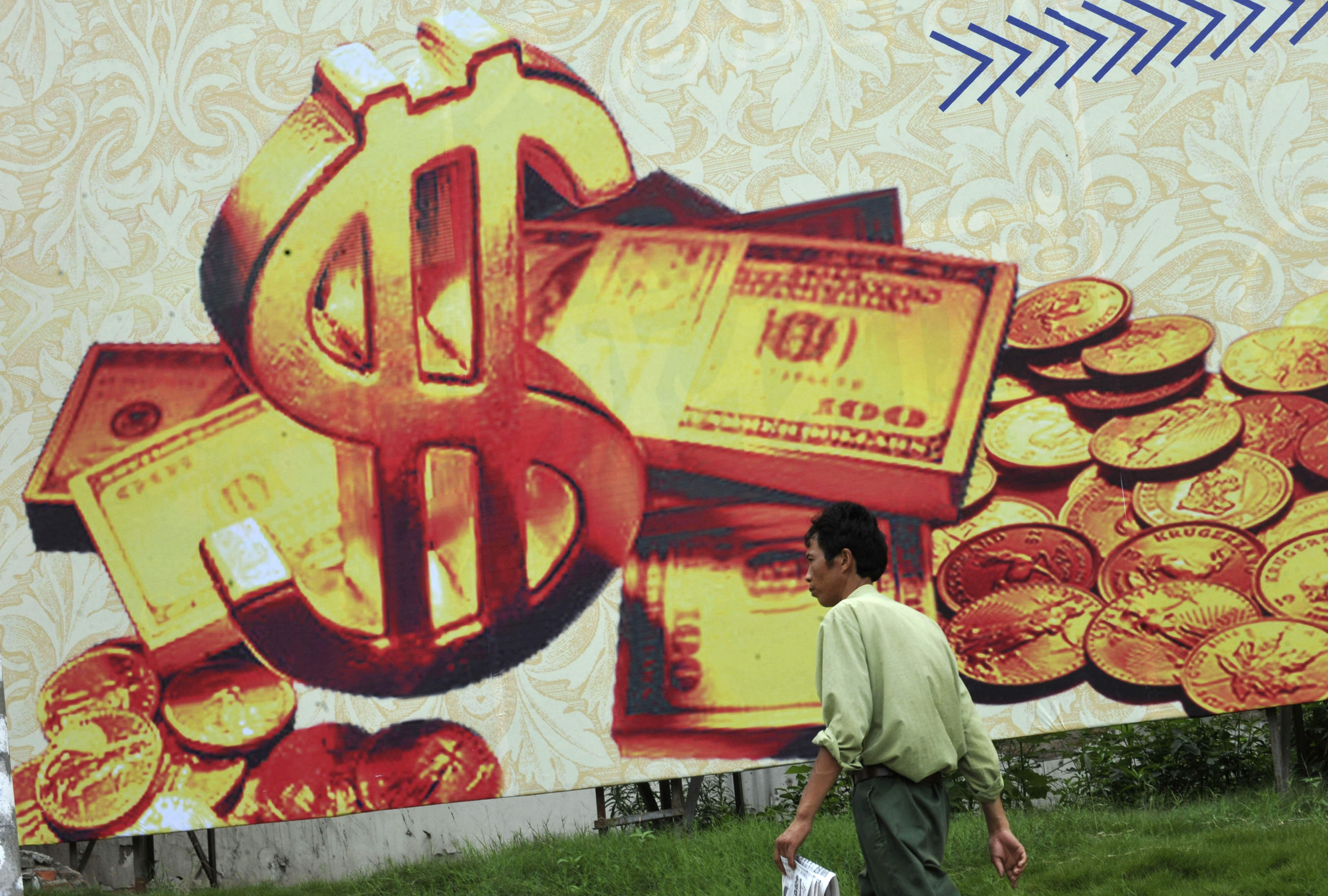 A man walks past a billboard featuring U.S. dollar notes on a street in Hefei, Anhui province July 8, 2010. China made clear again on Thursday that it has every intention of keeping its currency on a short leash with conditions not ripe, in its view, for the large appreciation sought by the United Sates. REUTERS/Stringer (CHINA - Tags: BUSINESS) CHINA OUT. NO COMMERCIAL OR EDITORIAL SALES IN CHINA - RTR2G7K0