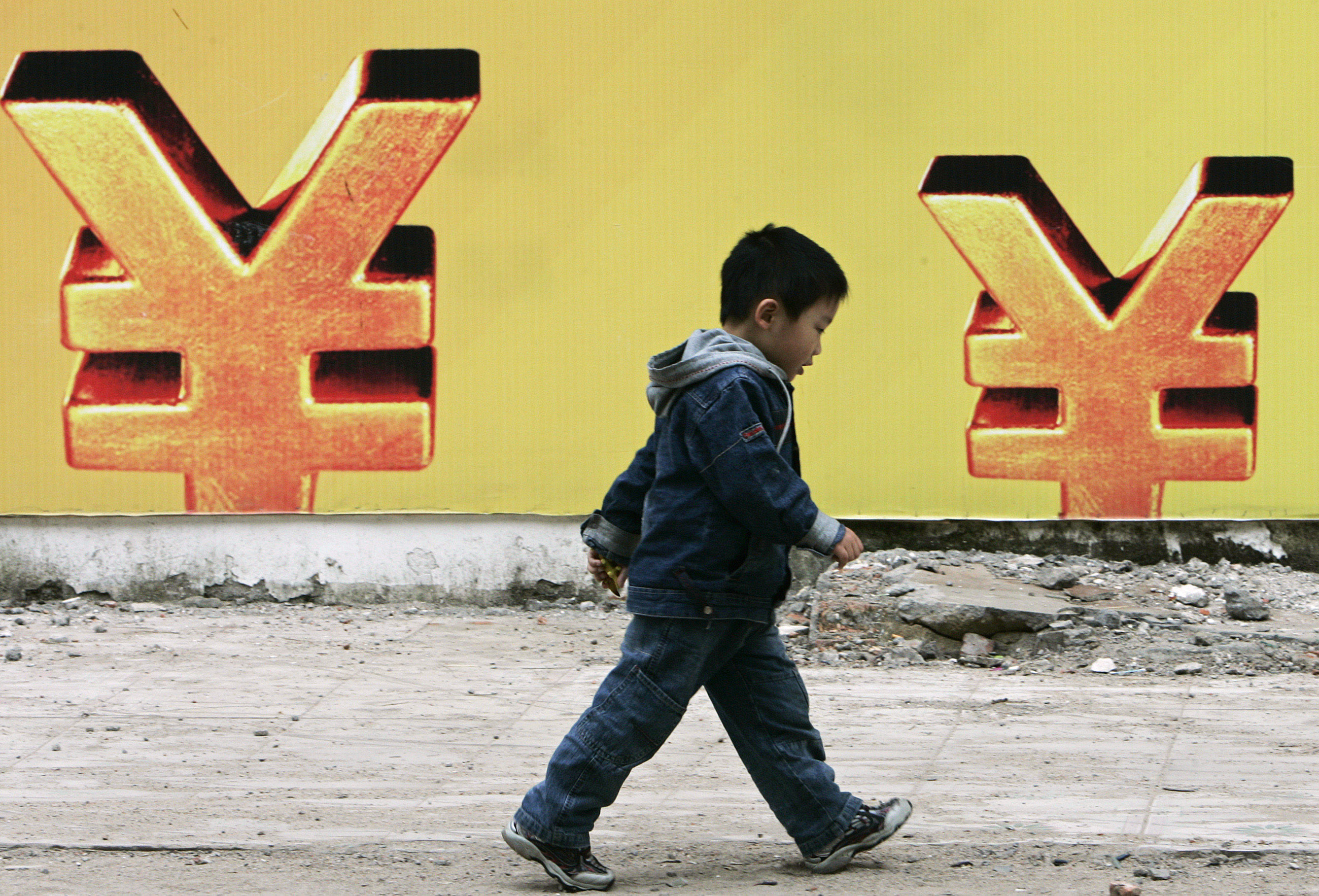 A boy walks past a billboard of the Renminbi (yuan) symbol in Haikou, south China's Hainan province, January 6, 2007. The yuan strengthened against the dollar late on Friday in line with other major Asian currencies, but trading remained sluggish after the new year holiday. REUTERS/Vito Lee (CHINA) - RTR1KX9M