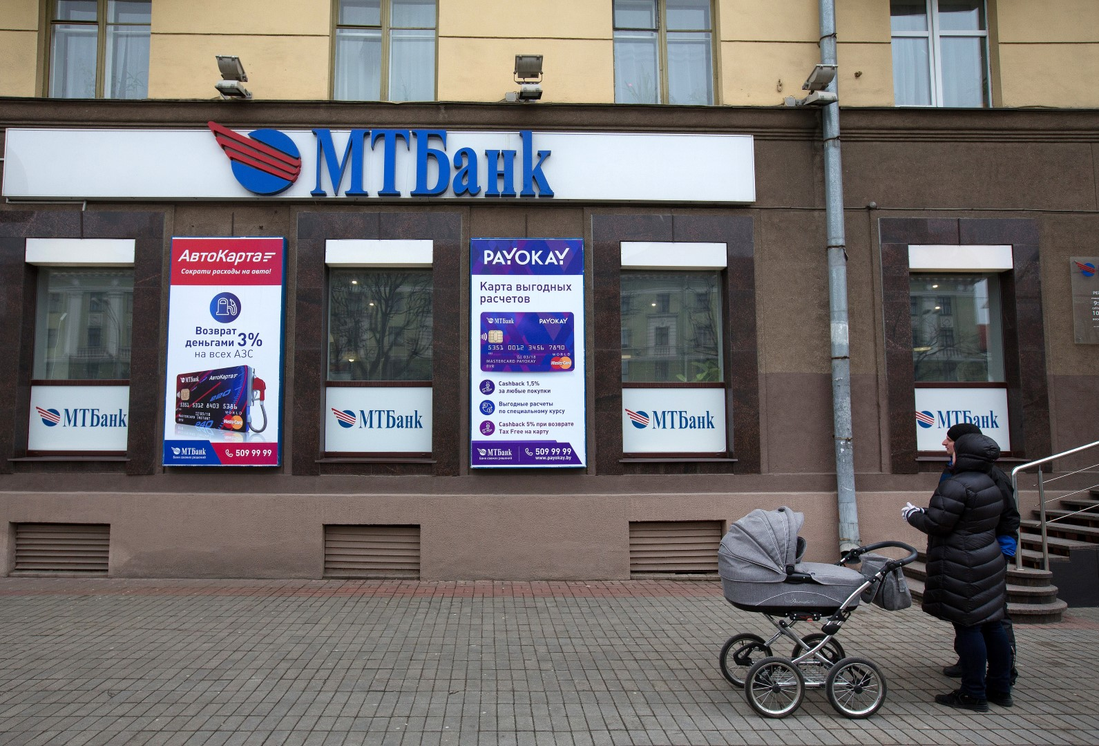 Pedestrians pause outside a branch of the Minsk Transit Bank CJSC, also known as MTBank, in Minsk, Belarus, on Wednesday, March 16, 2016. European Union governments scrapped sanctions on leaders of Belarus in an effort to pry the former Soviet republic out of the shadow of the Kremlin. Photographer: Andrey Rudakov/Bloomberg