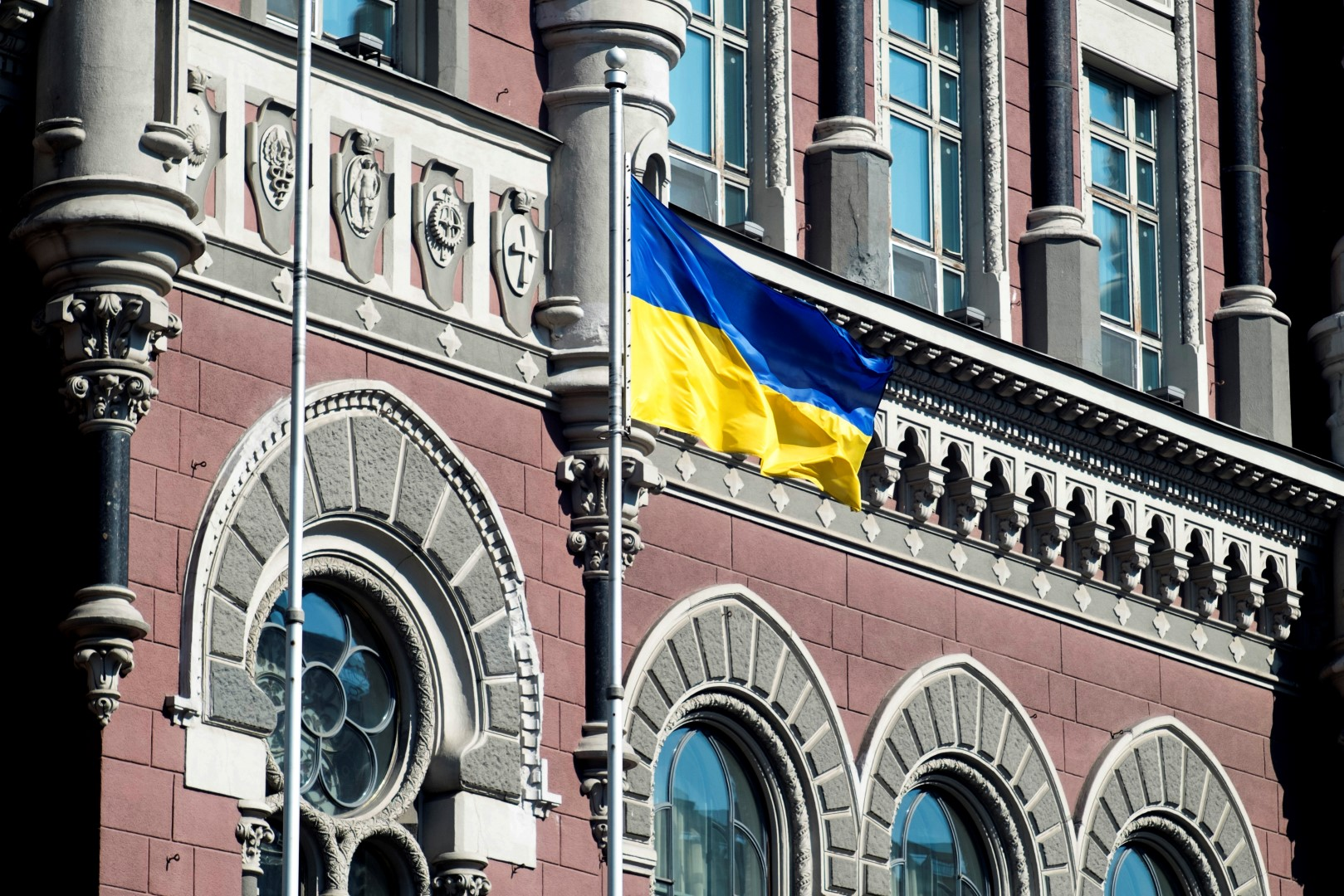 A Ukrainian national flag flies outside the Ukraine central bank in Kiev, Ukraine, on Friday, March 14, 2014. Ukraine's Eurobonds weakened and stocks headed for the worst week in seven on concern the conflict with Russia is intensifying two days before a referendum this weekend on the Crimean region's independence. Photographer: Vincent Mundy/Bloomberg
