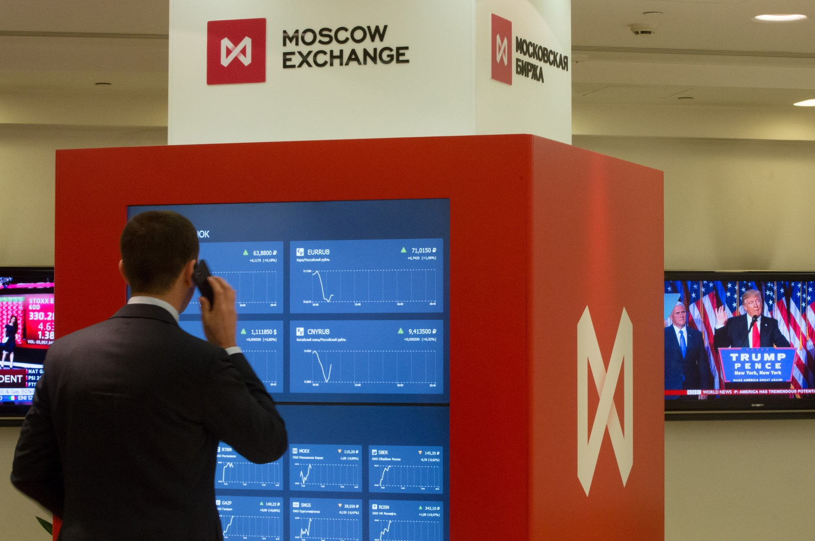 A visitor speaks on a smartphone while looking at financial information screens showing market reaction to the U.S. presidential election results at the Moscow Exchange in Moscow, Russia, Nov. 9, 2016. The ruble dropped as Donald Trump won the U.S. presidential race, driving down crude prices on concern his protectionist policies will sap global growth. Photographer: Andrey Rudakov/Bloomberg