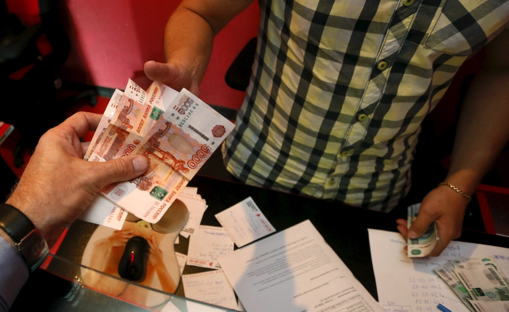 An employee (R) of a car service station takes Russian rouble banknotes from a client in the Siberian city of Krasnoyarsk, Russia, August 6, 2015. The Russian rouble fell on Thursday, continuing to reverse a recent rally after a renewed slide in the oil price below $50 a barrel. REUTERS/Ilya Naymushin - RTX1NBCU