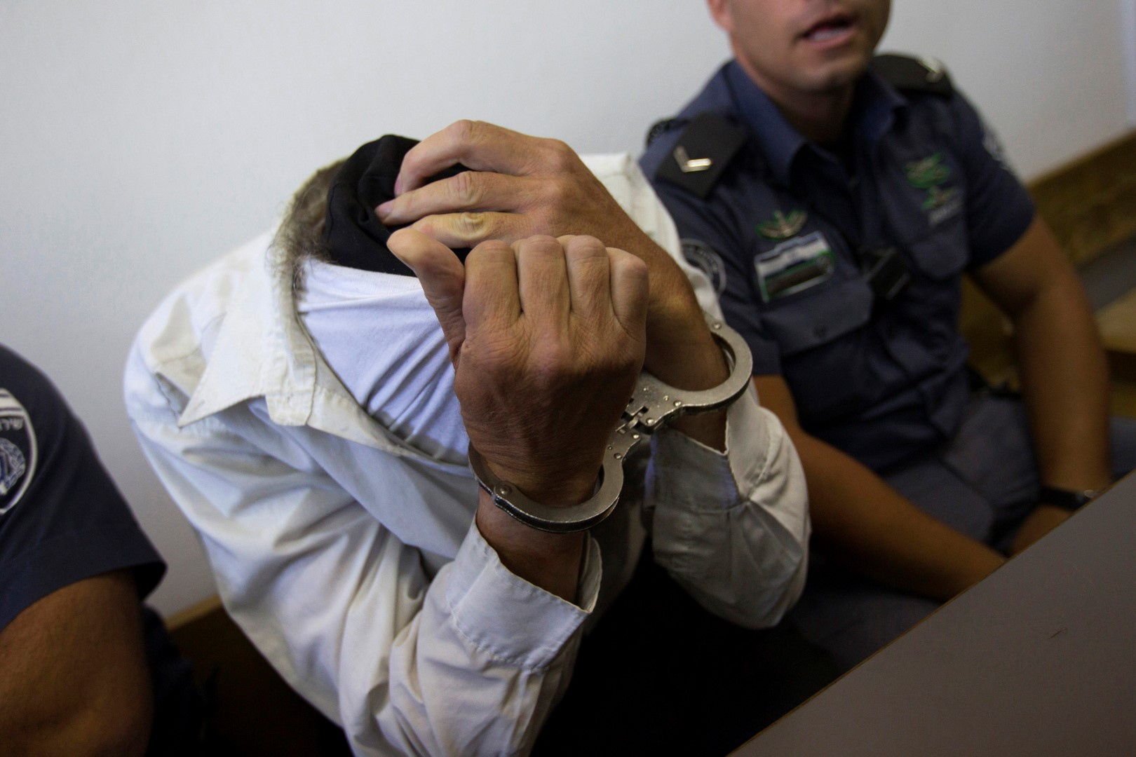 A man belonging to the fringe ultra-Orthodox Jewish group Neturei Karta covers his face at the Jerusalem District Court August 5, 2013. The man, an Israeli citizen, was charged last week with trying to spy for Iran. The Neturei Karta faction, a movement within the anti-Zionist bloc, believes a Jewish state should exist only after the Messiah comes. REUTERS/Ronen Zvulun (JERUSALEM - Tags: POLITICS CRIME LAW) - RTX12ASQ