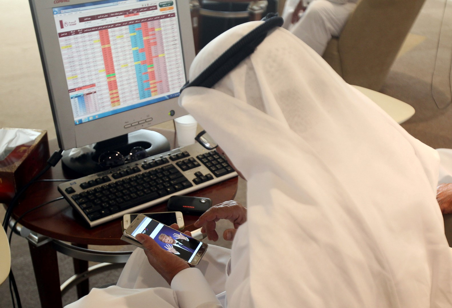 A trader uses his smartphone to follow news of U.S. presidential elections as he monitors a screen displaying stock information at Qatar Stock Exchange in Doha, Qatar November 9, 2016. REUTERS/Naseem Zeitoon  - RTX2SQ7Q