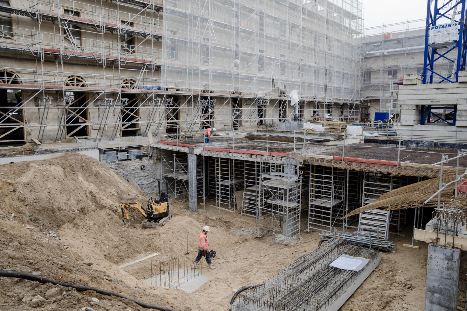 """A construction worker walks in an excavation at the Abbey of Penthemont as Vinci SA carry out renovation work on the 18th century building in Paris, France, on Thursday, Jan. 12, 2017. After months of muddling through, evidence is building that the euro area has finally embarked on what European Central Bank President Mario Draghi calls a """"moderate but firming recovery."""" Photographer: Marlene Awaad/Bloomberg"""