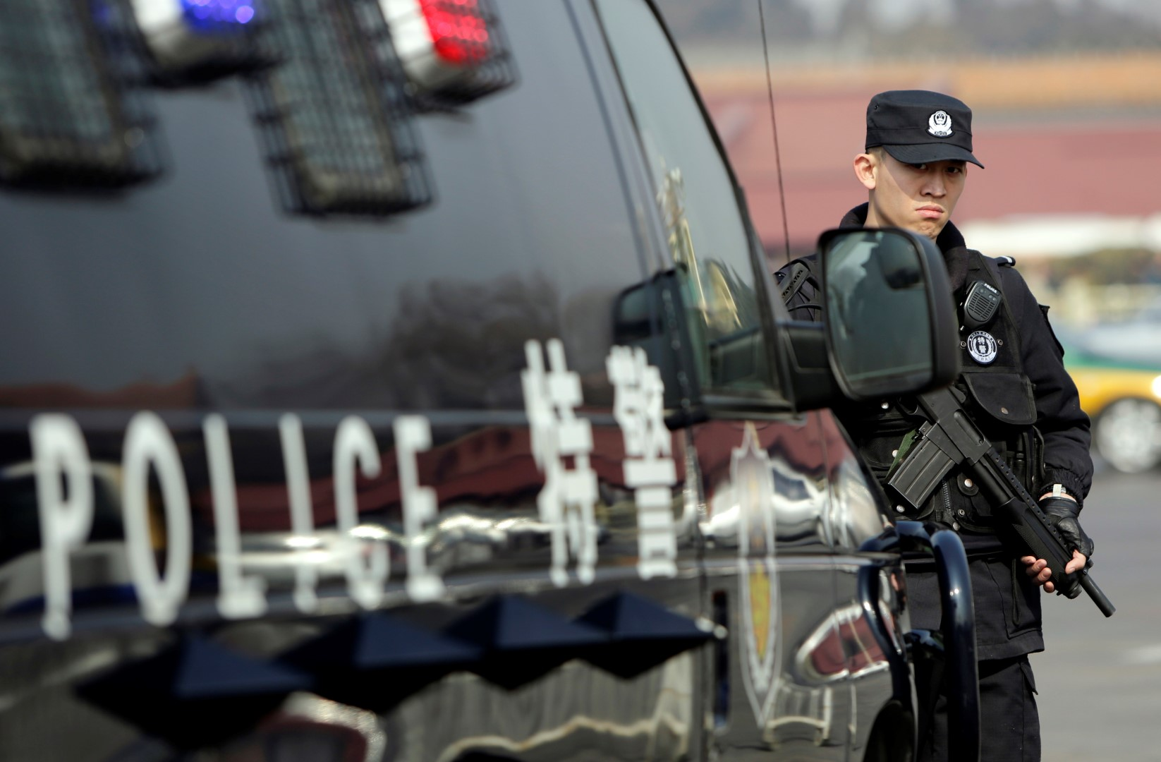 A policeman stands guard next to a vehicle of the Special Weapons and Tactics (SWAT) team on the Chang'an Avenue in front of the Tiananmen Square in Beijing ahead of the opening of the Chinese People's Political Consultative Conference (CPPCC), March 2, 2014. REUTERS/Jason Lee (CHINA - Tags: POLITICS MILITARY) - RTR3FW7J