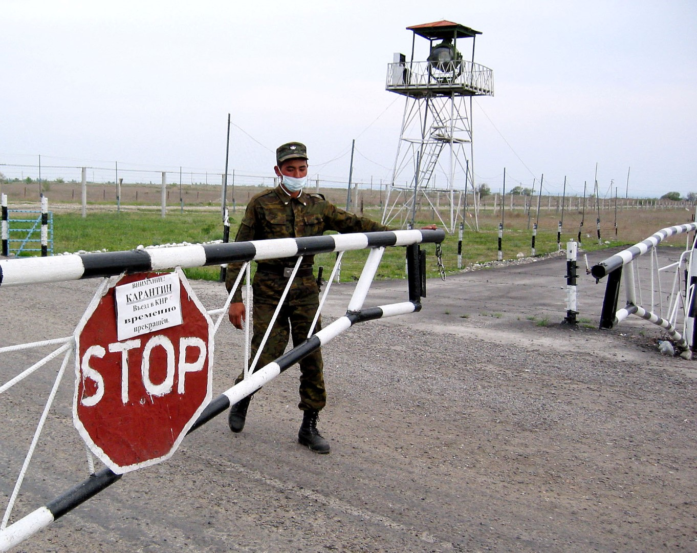 A border guard wearing a mask closes a barrier at the Korgas crossing point, the largest on the 1,500-km (940 mile) Kazakh-Chinese border on Tuesday, May 13, 2003. The barrier carries a sign announcing that entry to China has been temporarily suspended. Kazakhstan has closed its border with China to prevent the spread of Severe Acute Respiratory Syndrome, but no cases have so far been recorded in the former Soviet Central Asian state. TO ACCOMPANY FEATURE SARS-KAZAKHSTAN-CHINA REUTERS/Alexei Kalmykov AKA - RP3DRIIYJKAA