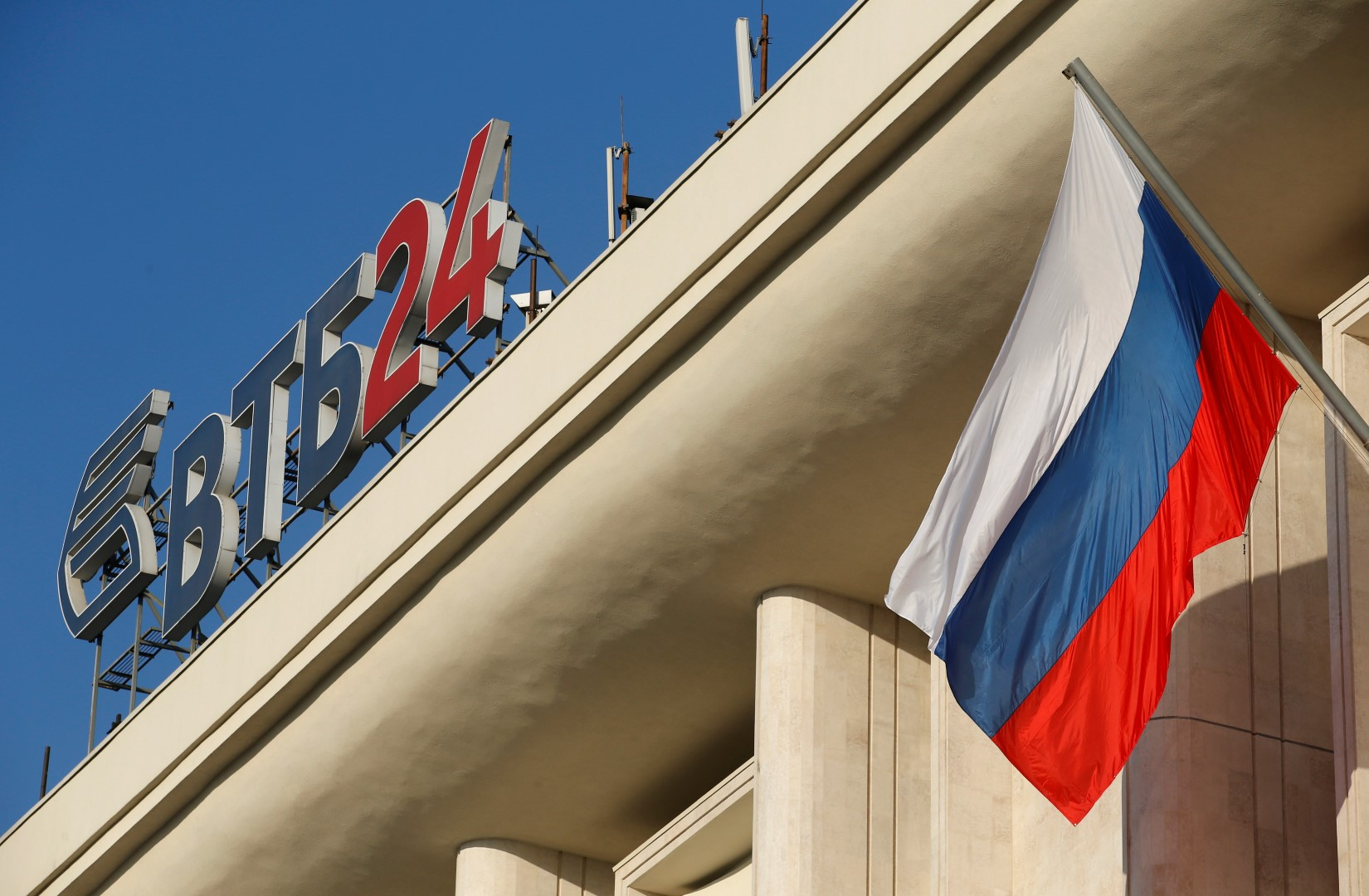 The logo of VTB Bank is displayed on the roof of a building, with a Russian national flag seen nearby, in Moscow, November 20, 2014. Russia's second-largest bank VTB said on Thursday its third-quarter net profit fell 98 percent year-on-year, dragged lower by higher provisions for bad loans and an economic slowdown. REUTERS/Maxim Zmeyev (RUSSIA - Tags: BUSINESS LOGO) - RTR4EUSH