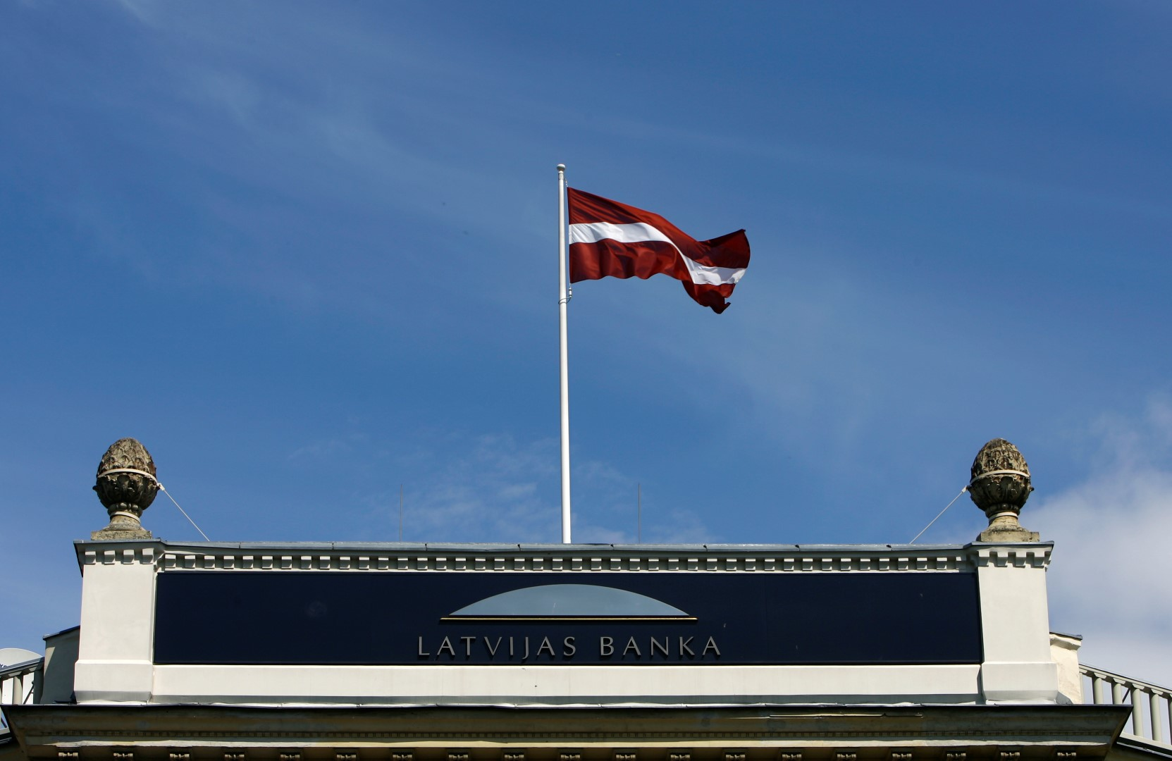 Latvia's flag waves over the Central Bank's main office building in Riga May 13, 2009. Latvia's central bank said on Wednesday it had revised its economic growth forecast to -16.5 percent from the previous forecast of -12.0 percent, and it had cut its refinancing rate to 4 percent from 5 percent. REUTERS/Ints Kalnins (LATVIA SOCIETY POLITICS BUSINESS) - GM1E55D1MDH01