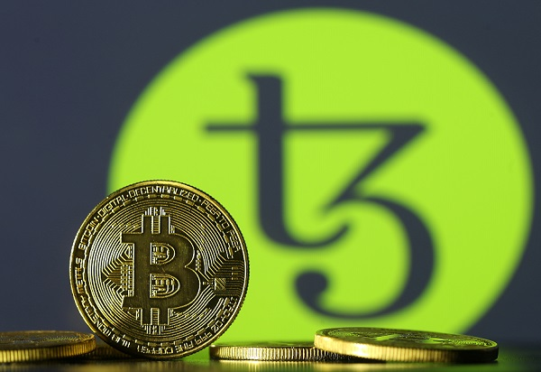 Photo illustration shows copies of Bitcoins seen in front of Tezos logo