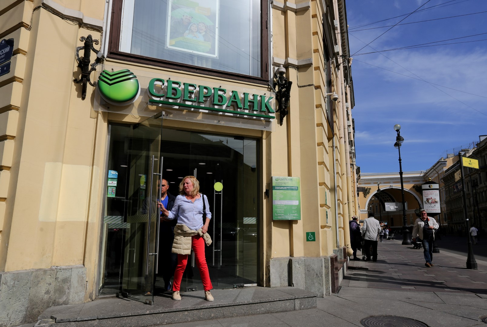 Customers exit a Sberbank PJSC bank branch ahead of the St. Petersburg International Economic Forum 2016 (SPIEF) in central Saint Petersburg, Russia, on Wednesday, June 15, 2016. The 20th anniversary St. Petersburg International Economic Forum which brings together heads of state and governments, political leaders, leading experts and global company executives runs from June 16-18. Photographer: Andrey Rudakov/Bloomberg