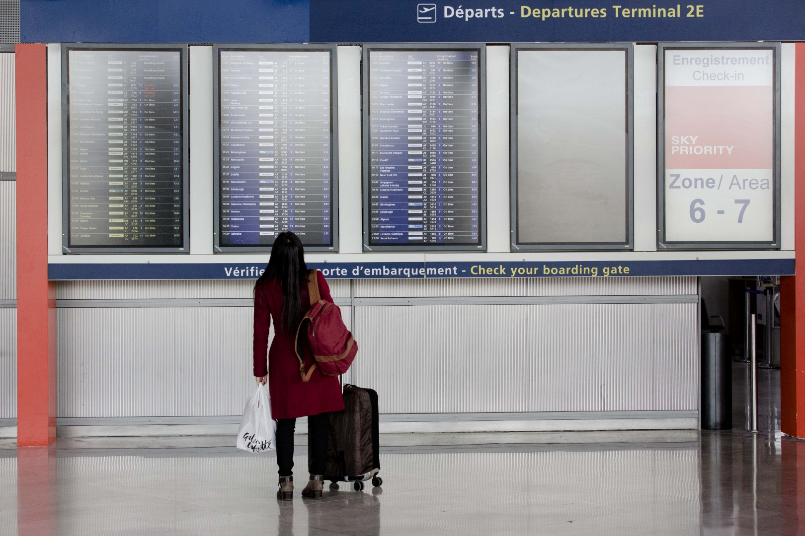 A passenger looks at flight departure information screens at Charles de Gaulle airport, operated by Aeroports de Paris, in Paris, France, on Thursday, Jan. 28, 2016. Air France-KLM Group Chief Executive Officer Alexandre De Juniac is negotiating with unions representing cabin and ground crews at the Air France brand and Dutch division KLM, as well as pilots at the French unit, after pulling a plan to expand its Transavia low-cost arm across Europe. Photographer: Marlene Awaad/Bloomberg