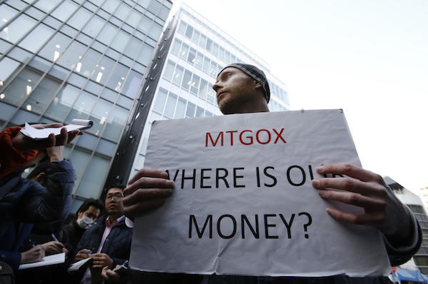 Burges, a self-styled cryptocurrency trader and former software engineer from London, holds a placard to protest against Mt. Gox in Tokyo
