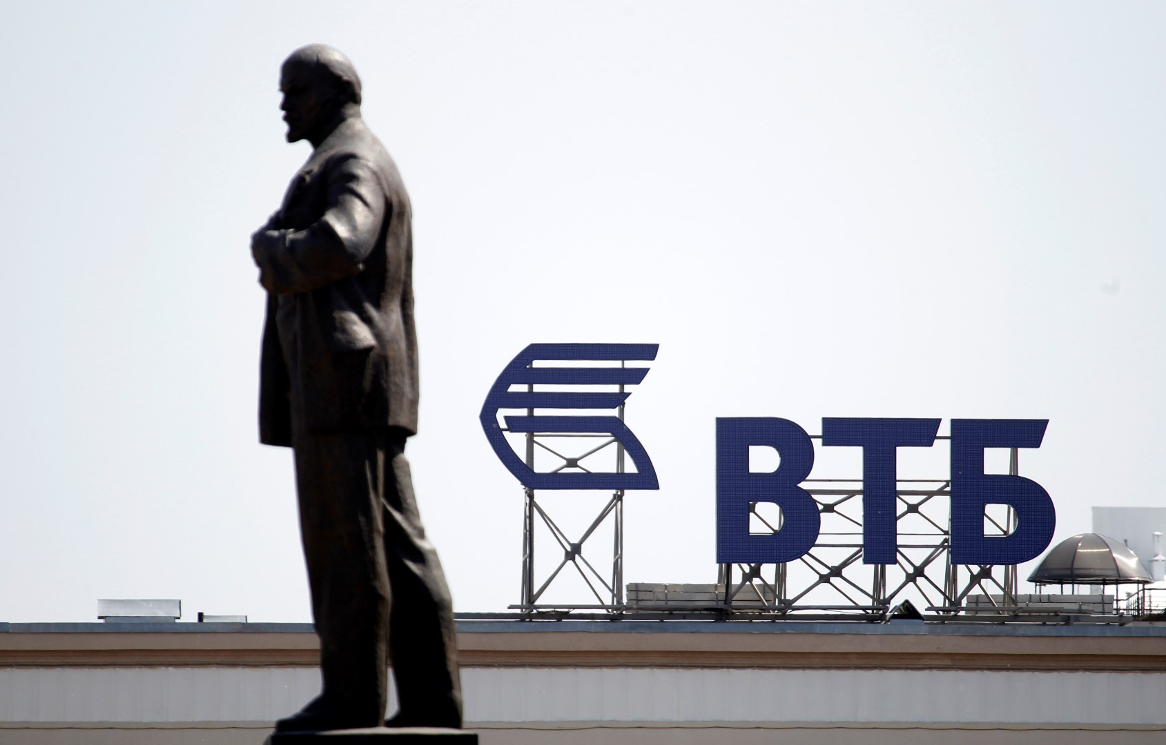 A sign for the logo of VTB Bank on the top of a building is pictured past a monument of Soviet state founder Vladimir Lenin in central Stavropol, southern Russia July 17, 2014. REUTERS/Eduard Korniyenko (RUSSIA - Tags: BUSINESS POLITICS LOGO CITYSCAPE) - GM1EA7H1O5F01