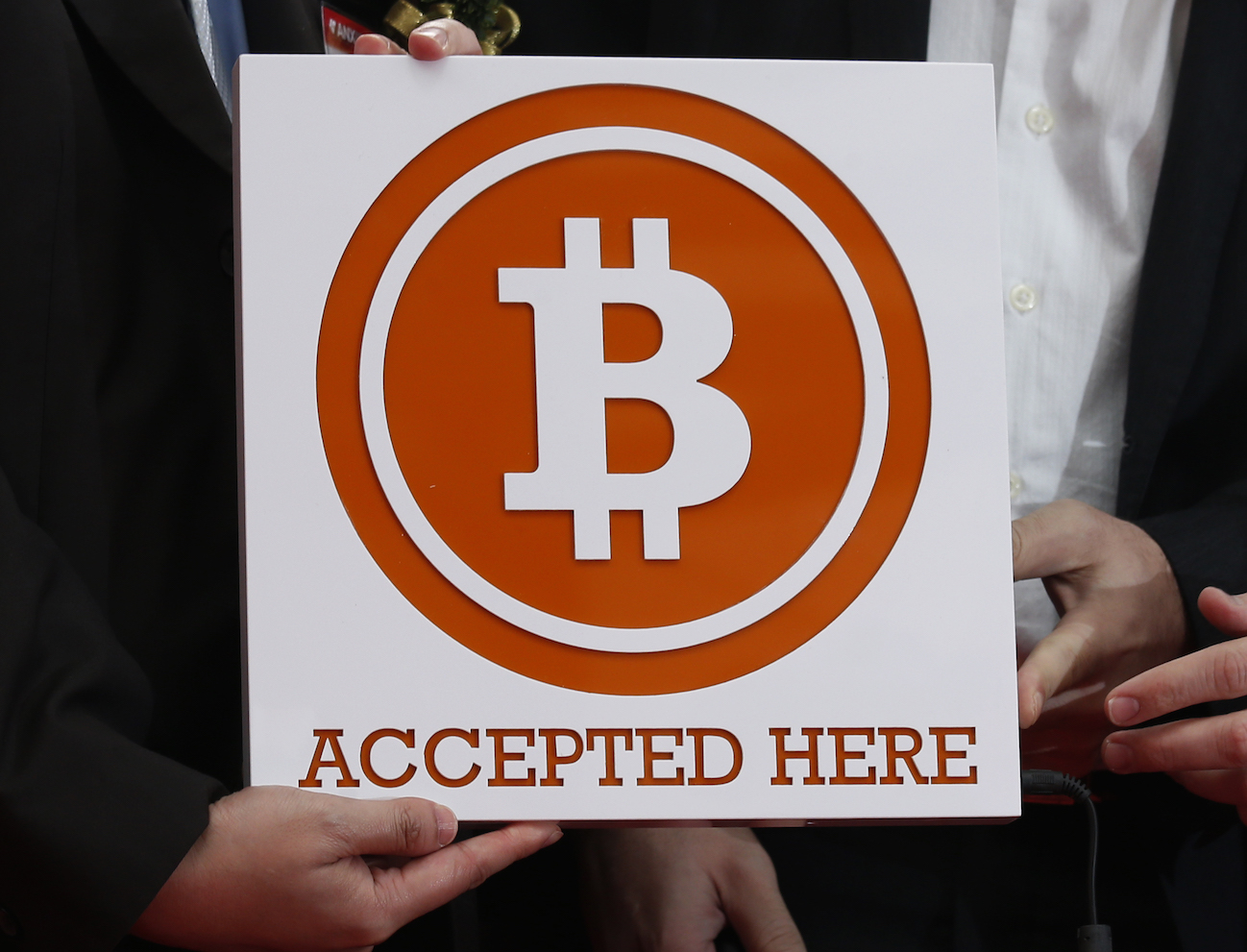 Bitcoin sign is held outside Hong Kong's first bitcoin retail store during its opening, in Hong Kong