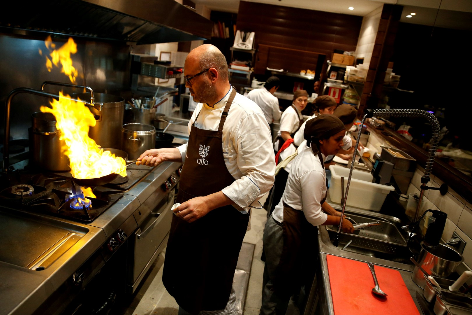 Chef Carlos Garcia (L) cooks within the kitchen of the Alto restaurant in Caracas, Venezuela June 29, 2017. Picture taken June 29, 2017. REUTERS/Ivan Alvarado - RC17E6B27420