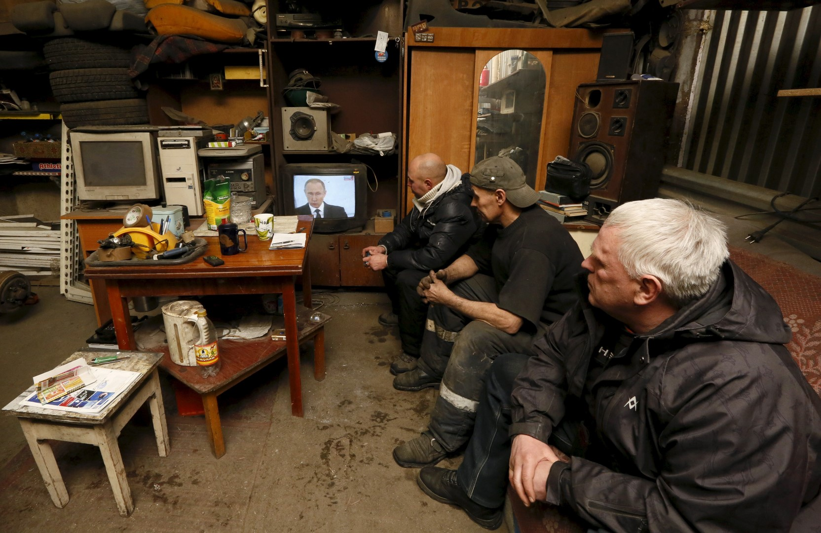 Workers watch a television broadcast of Russian President Vladimir Putin address to the Federal Assembly at an auto repair shop in the Siberian town of Divnogorsk near Krasnoyarsk, Russia, December 3, 2015. Putin used his annual state of the nation speech on Thursday to warn Turkey the Kremlin planned to adopt further sanctions against it to punish Ankara for shooting down a Russian warplane near the Syrian-Turkish border last week. REUTERS/Ilya Naymushin - GF20000083478