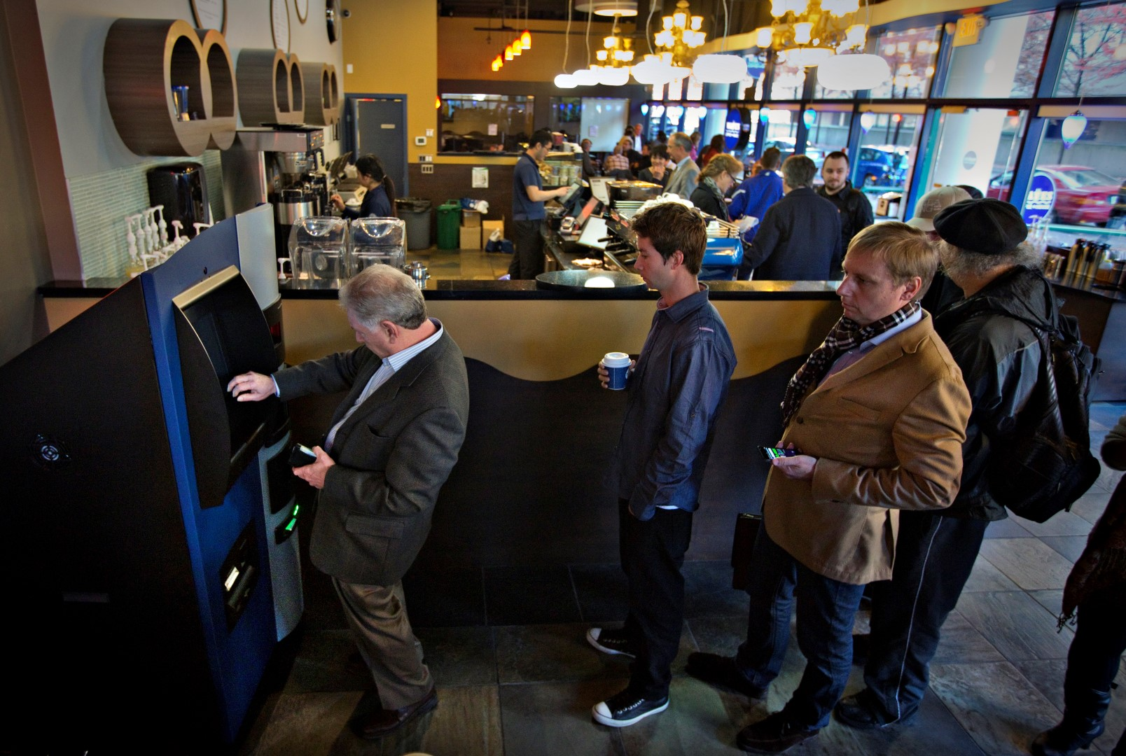 Customers line-up to use the world's first ever permanent bitcoin ATM unveiled at a coffee shop in Vancouver, British Columbia October 29, 2013. The kiosk, built by Las Vegas RoboCoin and operated by local dealer Bitcoiniacs, will allow users to withdraw their bit coins in the form of Canadian dollars or deposit cash to buy more bitcoins. REUTERS/Andy Clark (CANADA - Tags: BUSINESS SOCIETY SCIENCE TECHNOLOGY) - GM1E9AU08KU01