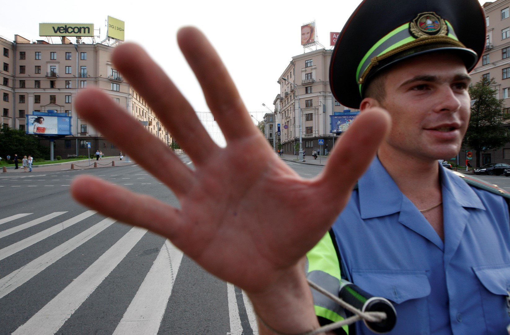 A traffic policeman tries to stop a photographer from taking pictures at an empty Independence avenue in central Minsk, July 21, 2011. The main street in Belarussian capital was blocked to prevent a protest rally against a rise in gasoline prices, which happened on Thursday. REUTERS/Vasily Fedosenko(BELARUS - Tags: CIVIL UNREST ENERGY) - GM1E77M089T01