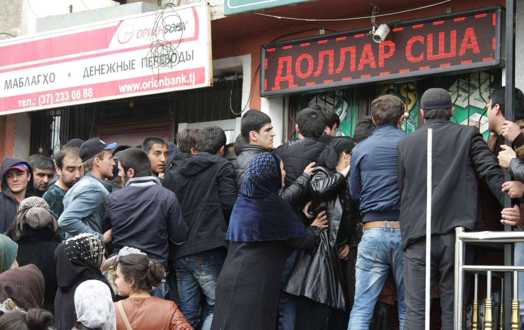 People gather near a currency exchange office in Dushanbe March 9, 2015. During the last week the average exchange rate of the U.S. dollar in the republic's exchange offices, rose and averaged 5.9930 - 6.0110 Tajikistan somoni, the National Bank of Tajikistan reported. In previous days, the average rates of exchange with the Russian rouble and the Euro also rose slightly and made 0,0960-0,0970 Somoni for one Russian rouble and 6.5990 - 6.6210 Somoni for one euro. REUTERS/Nozim Kalandarov (TAJIKISTAN  - Tags: BUSINESS) - GM1EB391GBZ01