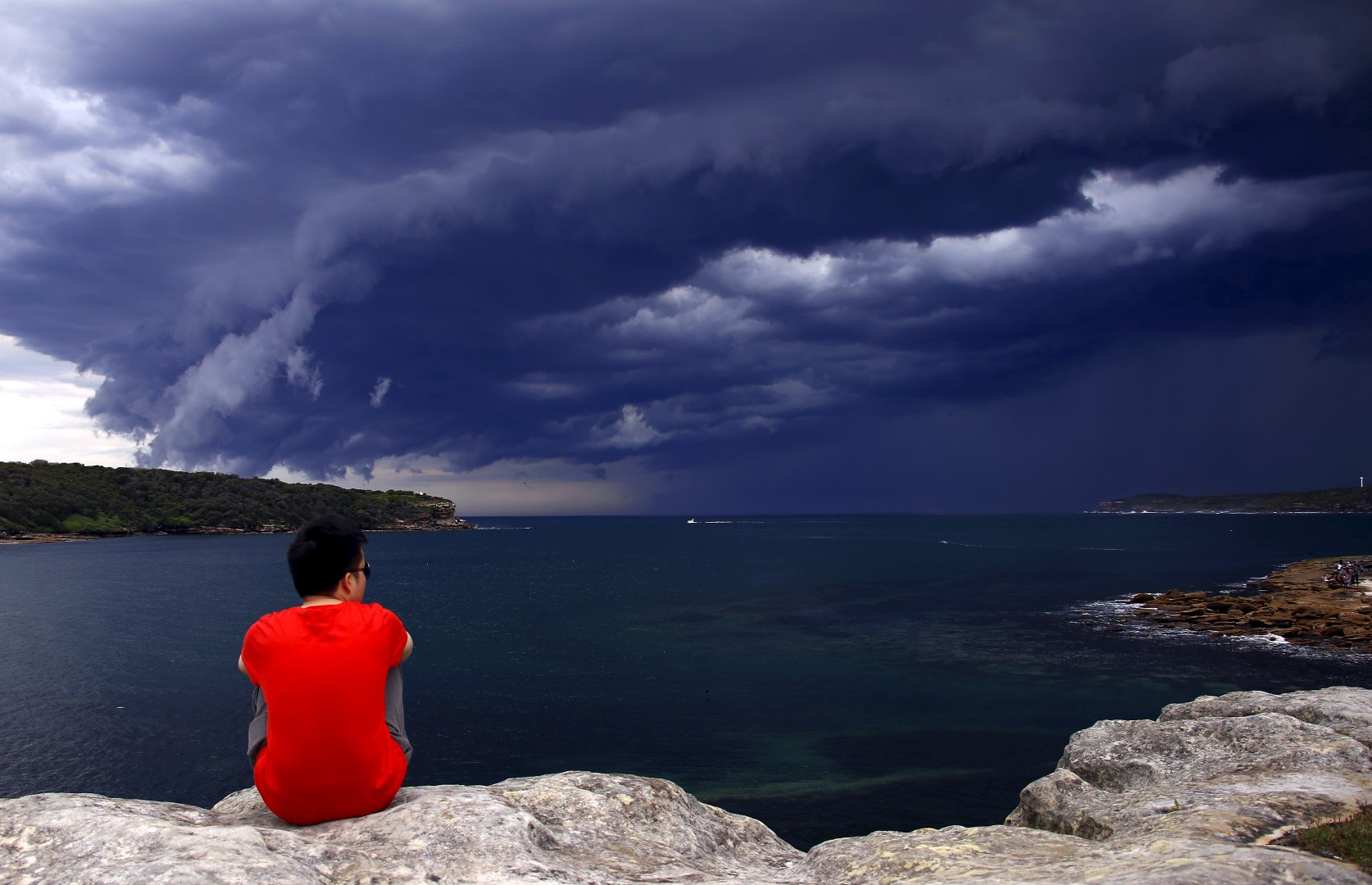 A Chinese tourist watches storm clouds moving along the coast towards the city of Sydney, Australia, November 6, 2015. Powerful storms swept across the city on Friday, with the Australian Bureau of Meteorology issuing a warning for severe thunderstorms with large hailstones, heavy rainfall and damaging winds, local media reported. REUTERS/David Gray - GF20000047792