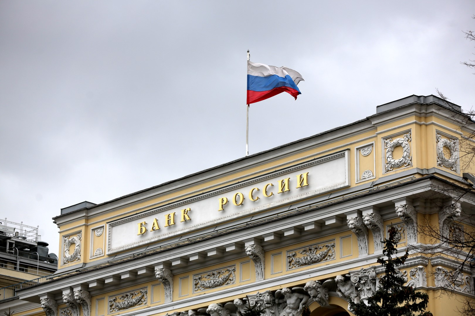 """The flag of the Russian Federation flies above the headquarters of the Russian central bank, also known as Bank Rossii, in Moscow, Russia, on Friday, March 18, 2016. Russia's central bank kept its benchmark interest rate unchanged for a fifth meeting amid risks to inflation, warning that its """"moderately tight"""" monetary policy may last longer than previously planned. Photographer: Andrey Rudakov/Bloomberg"""