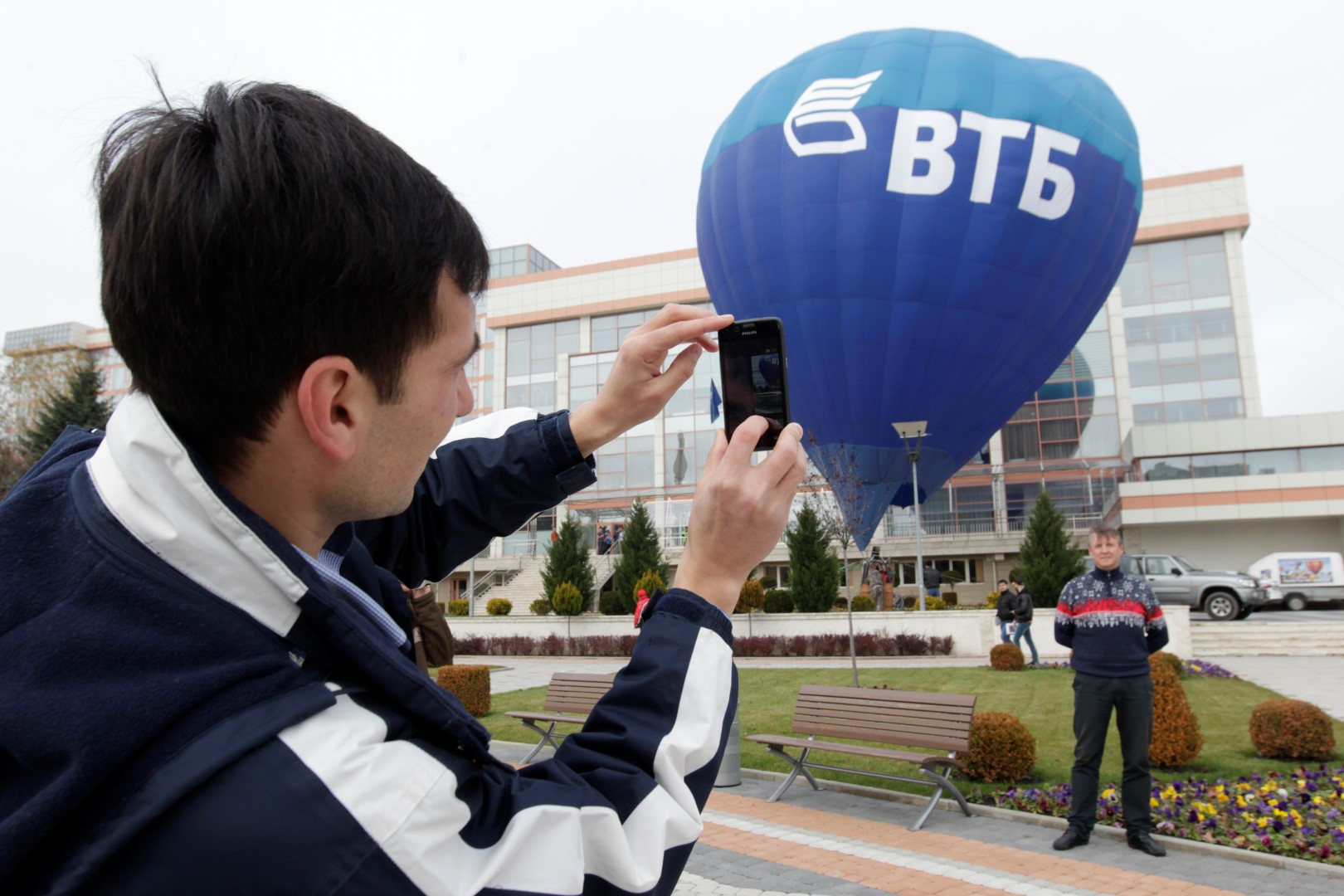 People take pictures in front of an air balloon, with the logo of VTB Bank displayed on it, in Essentuki, southern Russia, October 31, 2014. Russia's second-largest bank VTB expects a tough end to the year after posting a 98 percent slide in third-quarter profit because of higher provisions for bad loans, an economic slowdown and losses over Ukraine. Picture taken October 31, 2014. REUTERS/Eduard Korniyenko (RUSSIA - Tags: BUSINESS) - GM1EABL03MX01