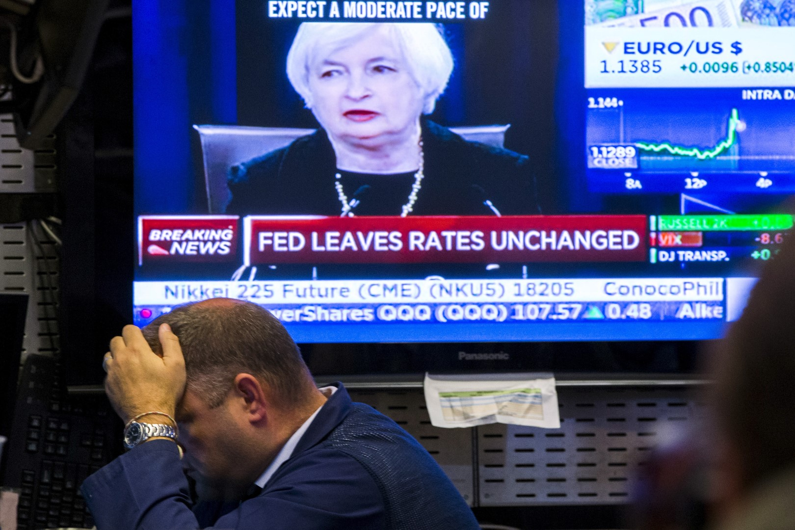 A trader works underneath a television screen showing Federal Reserve Chair Janet Yellen announcing that the Federal Reserve will leave interest rates unchanged on the floor of the New York Stock Exchange in New York September 17, 2015. REUTERS/Lucas Jackson - RTS1MCU