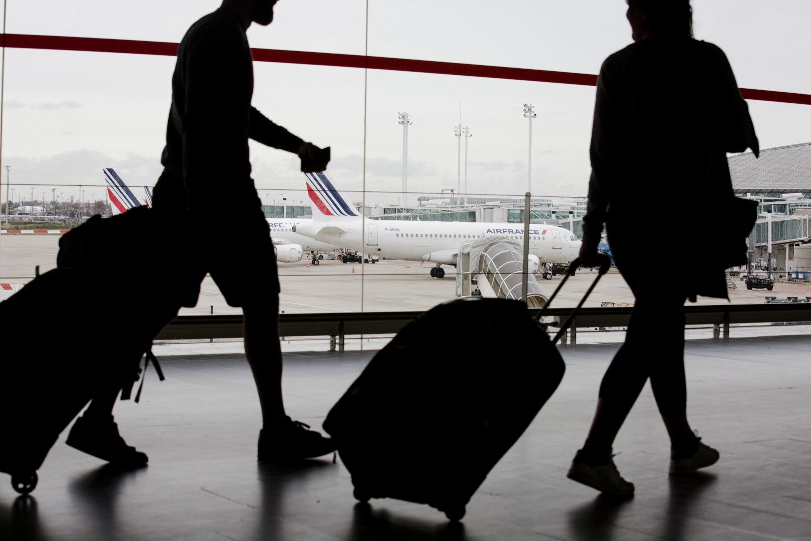 Passengers pull their luggage inside a terminal building as an Air France aircraft, operated by Air France-KLM Group, stand on the tarmac beyond, at Charles de Gaulle airport, operated by Aeroports de Paris, in Paris, France, on Thursday, Jan. 28, 2016. Air France-KLM Group Chief Executive Officer Alexandre De Juniac is negotiating with unions representing cabin and ground crews at the Air France brand and Dutch division KLM, as well as pilots at the French unit, after pulling a plan to expand its Transavia low-cost arm across Europe. Photographer: Marlene Awaad/Bloomberg