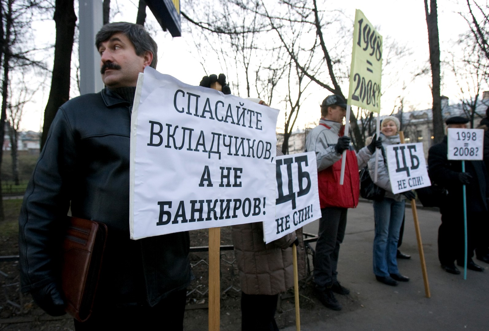 """Investors of the bank Kapital Kredit stand with placards reading (L-R) """"Save Investors, Not Bankers"""", """"Central Bank, Wake Up!"""" and """"1998 (Crisis) equals 2008"""" during a picket in front of the main building in Moscow, December 19, 2008. Bank investors gathered to claim their money from the bank.  REUTERS/Sergei Karpukhin  (RUSSIA) - GM1E4CJ1SDH01"""
